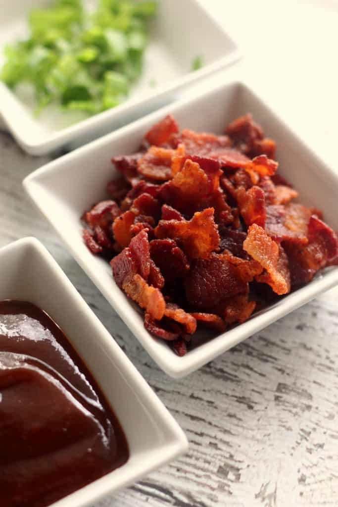 BBQ Chicken Dip Recipe | Bacon, green onions, and BBQ sauce in white ramekins