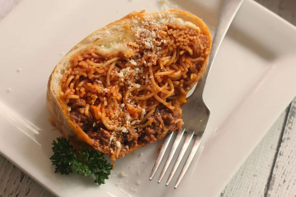 Spaghetti Stuffed Garlic Bread on a white plate with parsley and parmesan cheese
