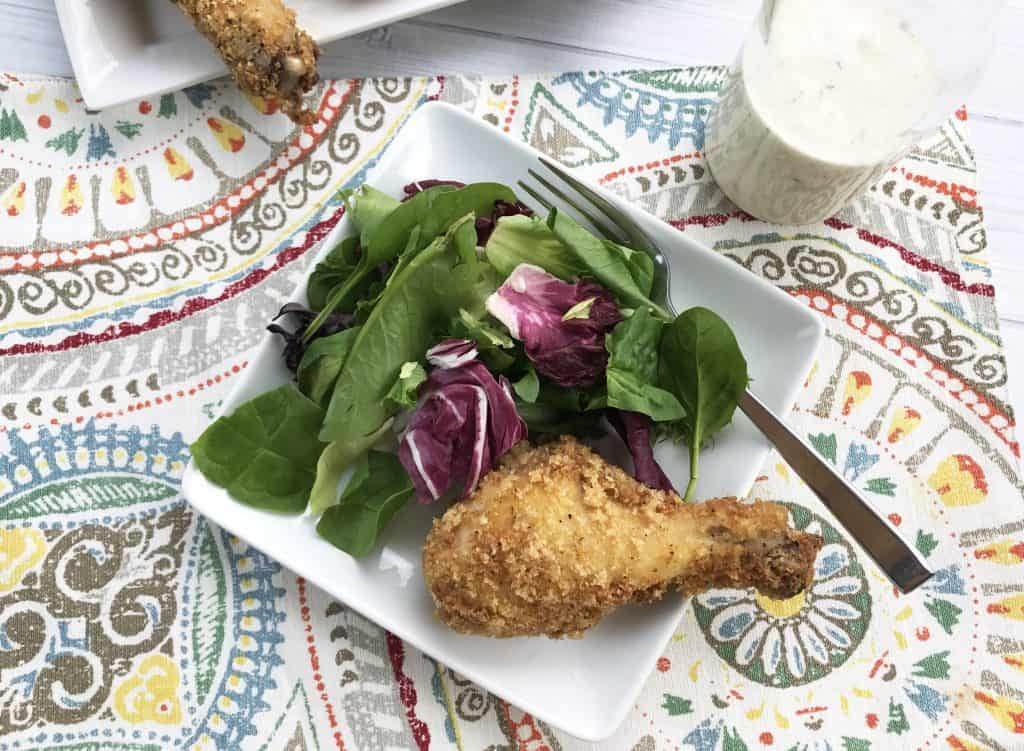 Keto Chicken Legs on a white plate with a salad