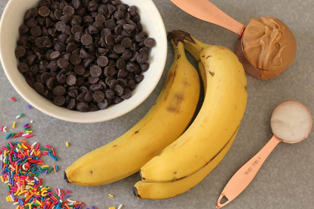 Semi-sweet chocolate chips, bananas, sprinkles, and peanut butter ready to be turned into Chunky Monkey Peanut Butter Banana Bites