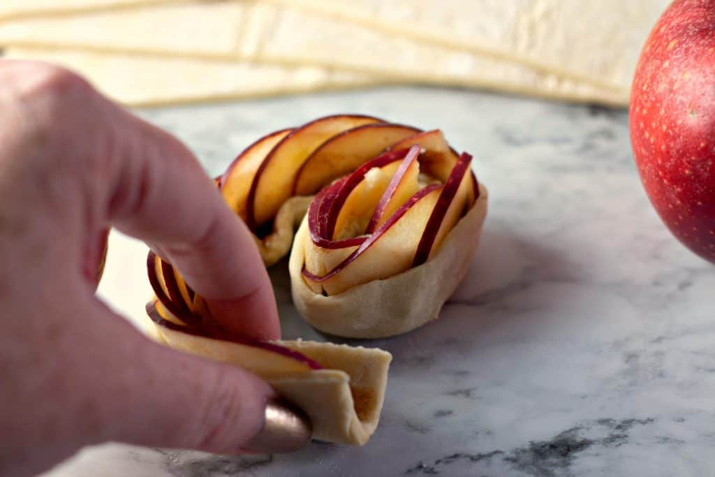 Coiling apples in puff pastry to make Caramel Apple Rose Tarts