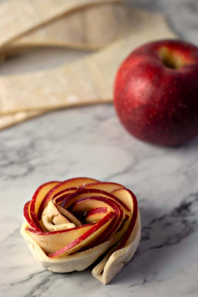 Caramel Apple Rose Tarts on a marble counter with a red apple in the background