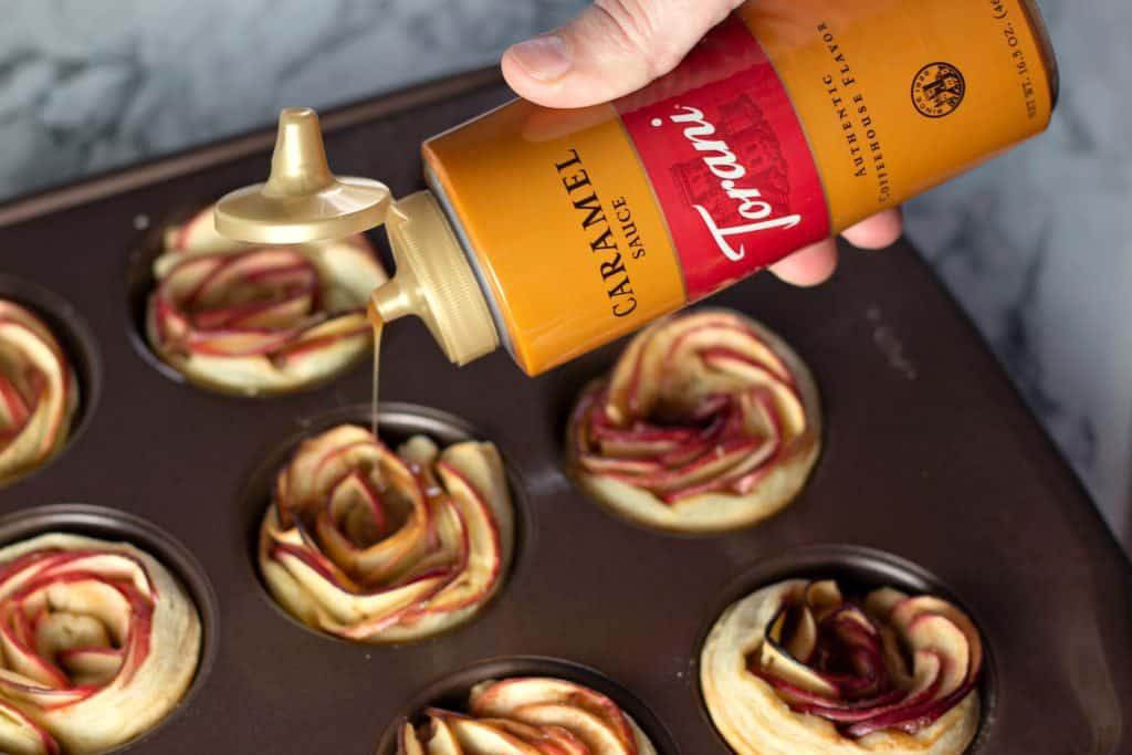 Drizzling Torani Caramel Sauce onto baked Caramel Apple Rose Tarts