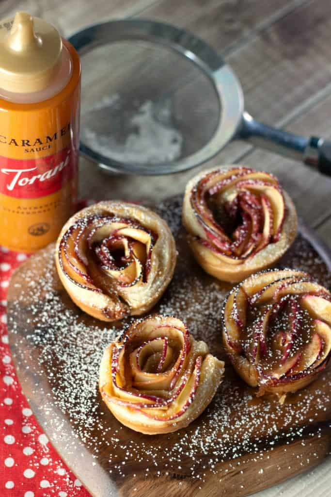 Caramel Apple Rose Tarts dusted with powdered sugar on a rustic wood platter