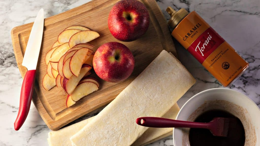 Slicing tart red apples on a bamboo cutting board on a marble counter for making Caramel Apple Rose Tarts