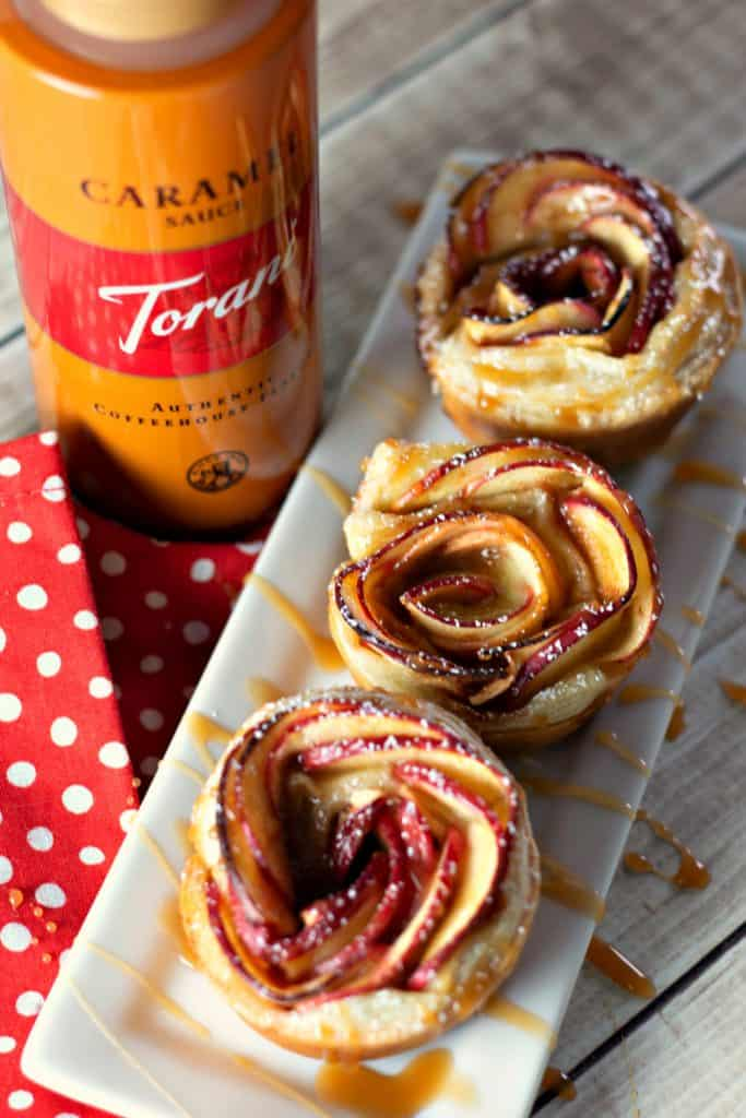 Caramel Apple Rose Tarts on a white rectangle place drizzled with Troani Caramel Sauce with a red and white polka dot napkin