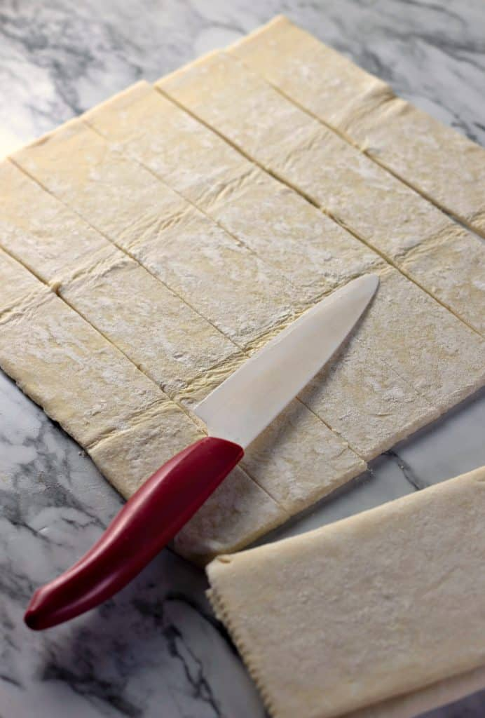 Slicing puff pastry into strips for making Caramel Apple Rose Tarts
