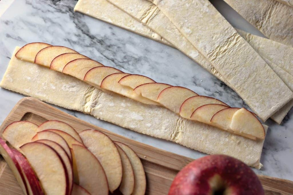 Placing sliced apples onto strips of puff pastry for making Caramel Apple Rose Tarts