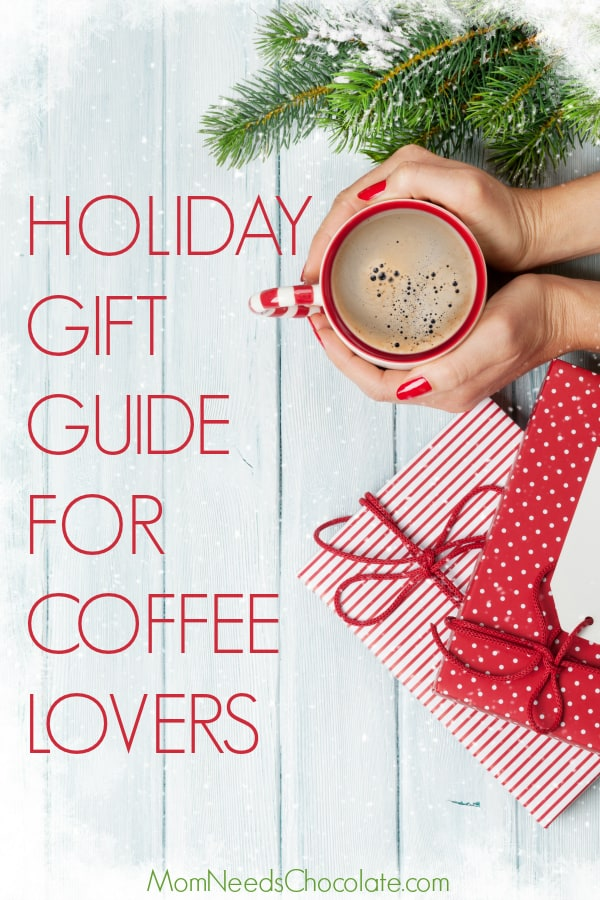 Holiday Gift Guide for the Coffee Lover - Female hands holding coffee cup, christmas gift boxes and snow fir tree above wooden table. Top view with copy space