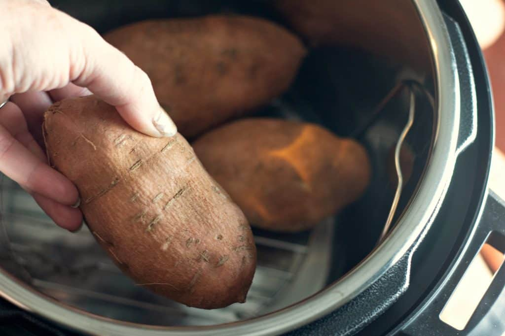 Placing sweet potatoes into an Instant Pot to make Instant Pot Sweet Potatoes