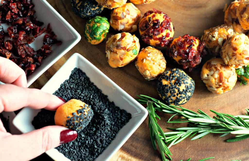 Rolling mini cheese balls in black sesame seeds