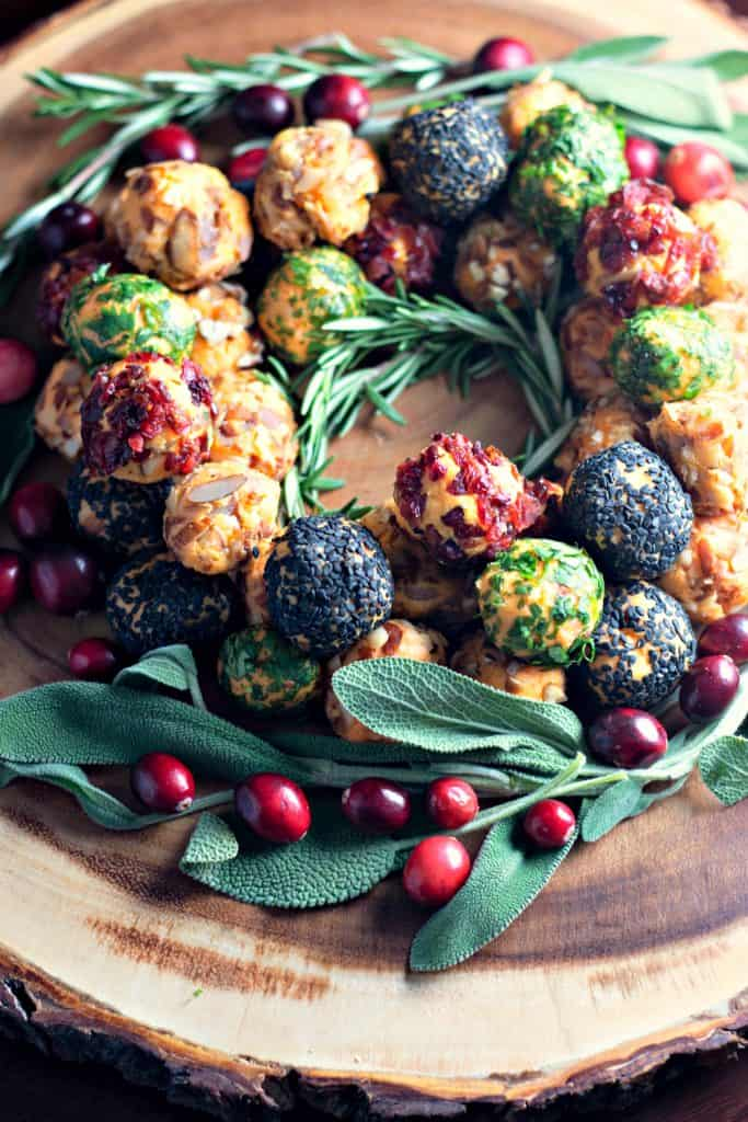 Holiday Cheese Ball Wreath on a rustic wood serving platter surrounded by sage and cranberries