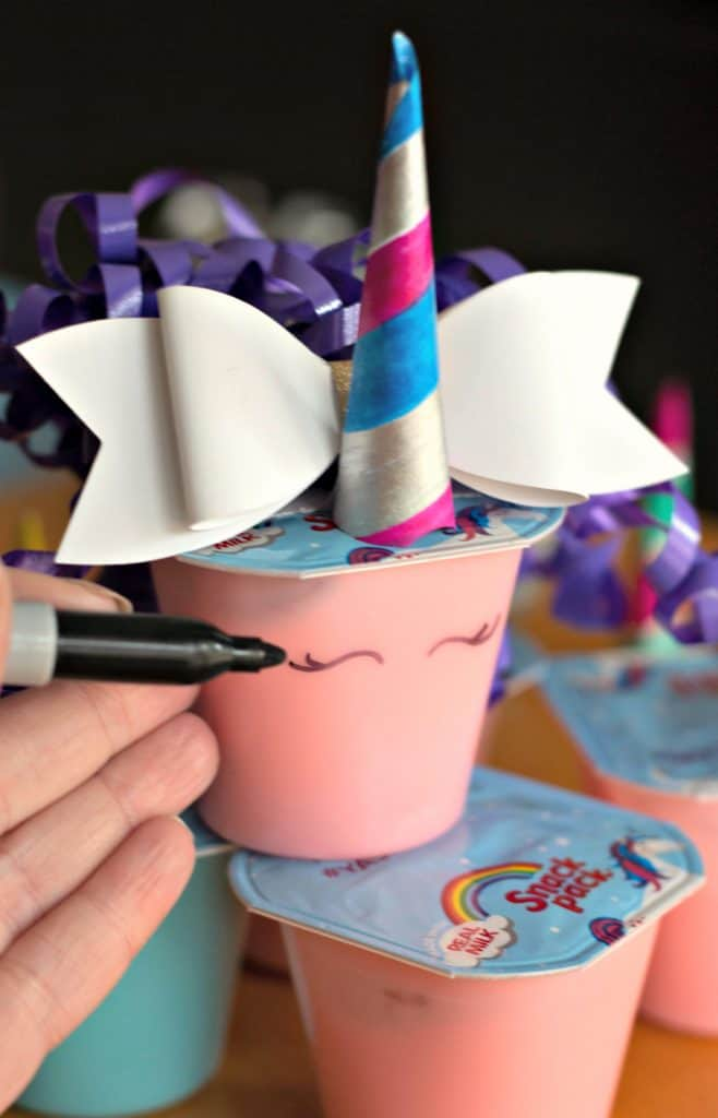 Drawing eyes on a Unicorn Pudding Cups Craft