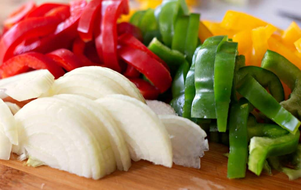 Sliced onion and three colors of bell peppers for making Pierogi Skillet
