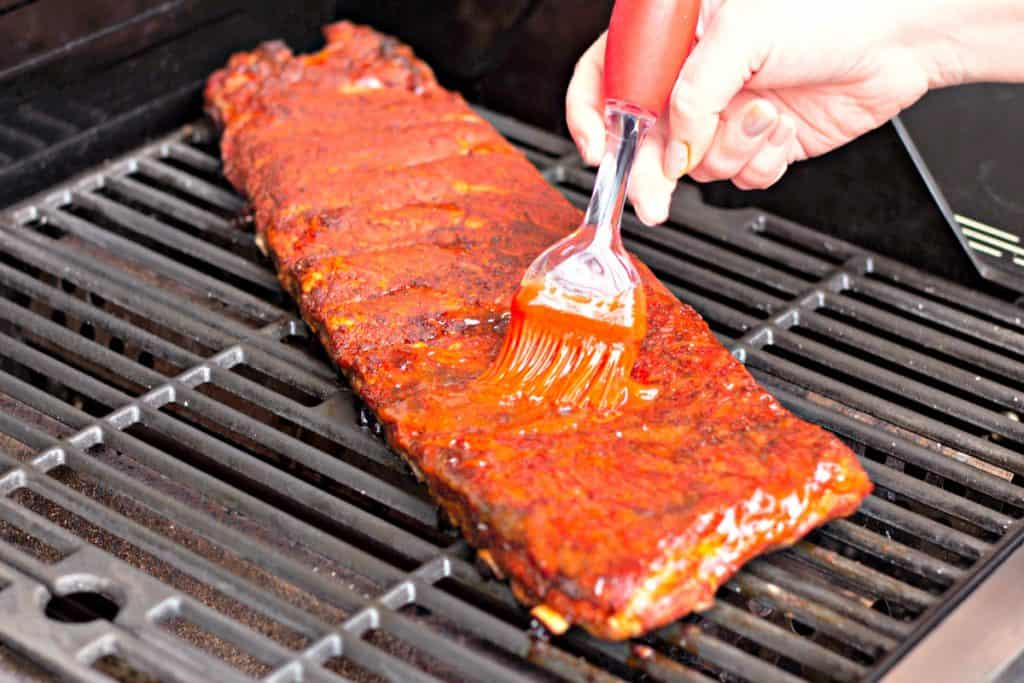 Brushing BBQ sauce on grilled ribs