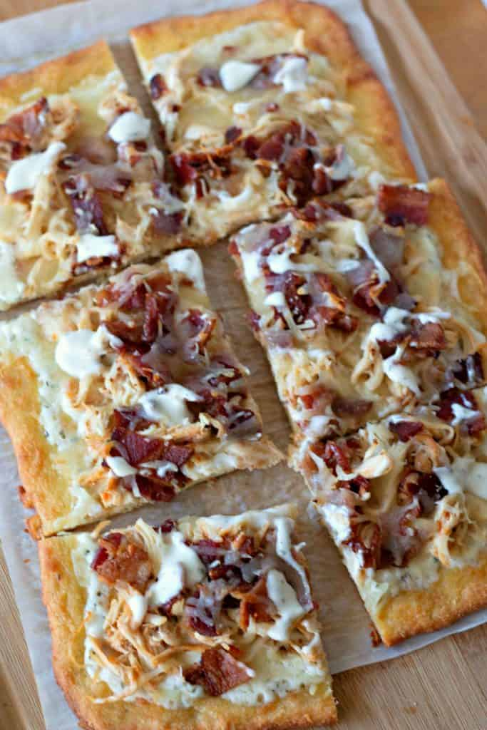 "Eating low carb but missing pizza? No need to miss out! This Keto Chicken Bacon Ranch Pizza will calm your pizza craving while not messing up your eating plan. A ""fat head"" pizza crust loaded with shredded chicken, crispy bacon, mozzarella cheese, and creamy ranch dressing; what's not to love about this?! #Keto #KetoRecipes #KetoPizza #GlutenFree #GlutenFreePizza #GlutenFreeRecipes #LowCarb #Bacon #MomNeedsChocolate"