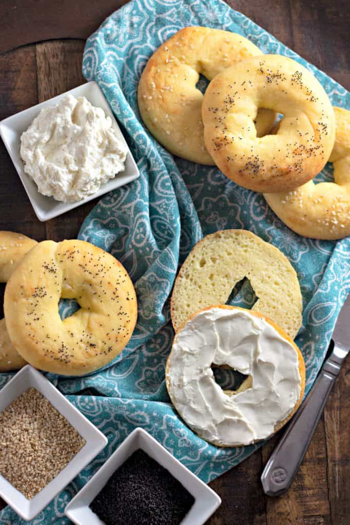 The Perfect Keto Bagels topped with poppy seeds and sesame seeds with cream cheese on a Mary and Martha wooden ampersand tray and a blue Pioneer Woman napkin from Walmart