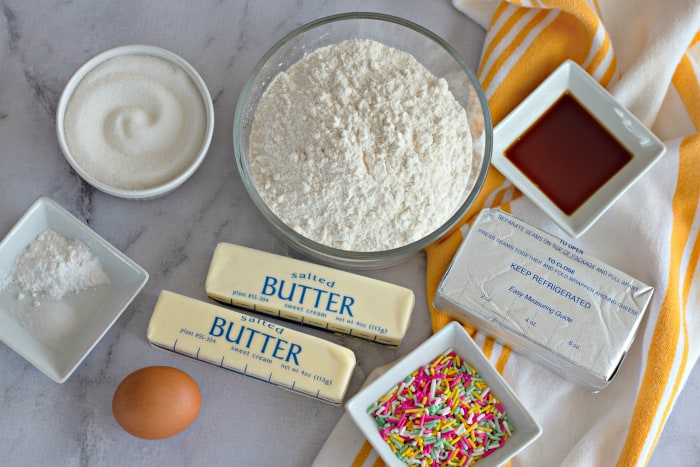 Ingredients to make Cream Cheese Sprinkle Cookies on a marble counter