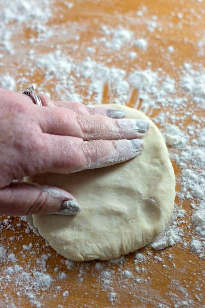Flattening Homemade Flour Tortillas on a floured wood surface