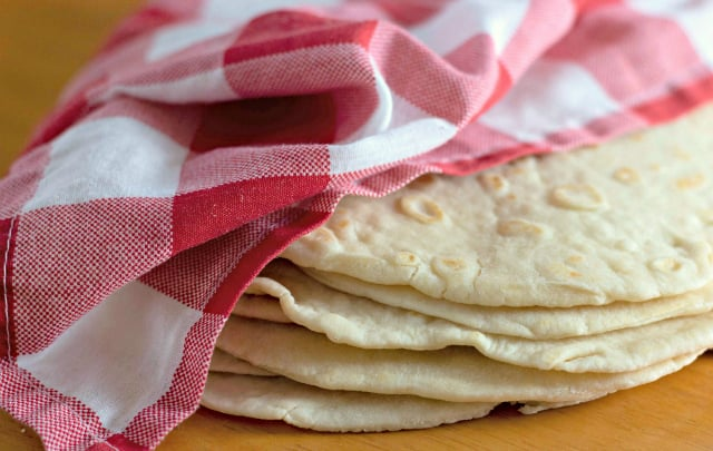 Homemade Flour Tortillas wrapped in a red and white checkered napkin