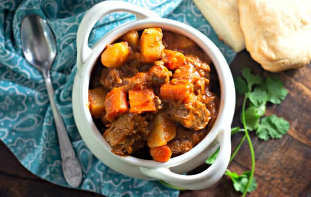 Pot Roast Beef Stew Recipe in a white bowl on a light blue napkin