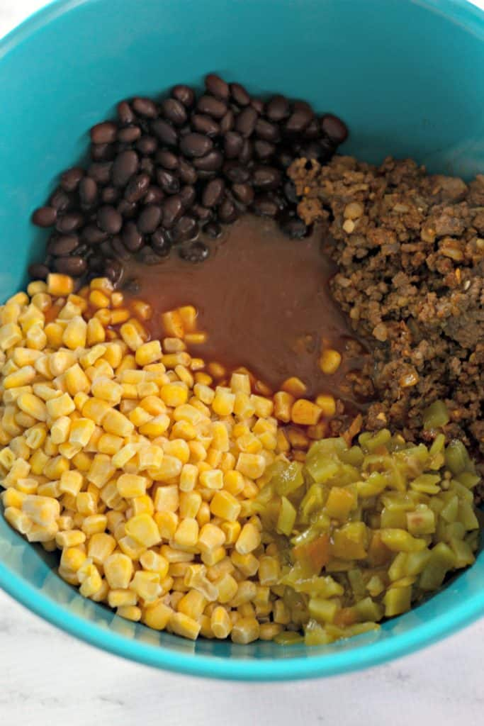 Mixing ingredients for Tater Tot Taco Casserole in a teal blue bowl