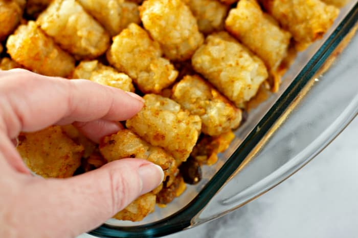 Placing tater tots on a Tater Tot Taco Casserole