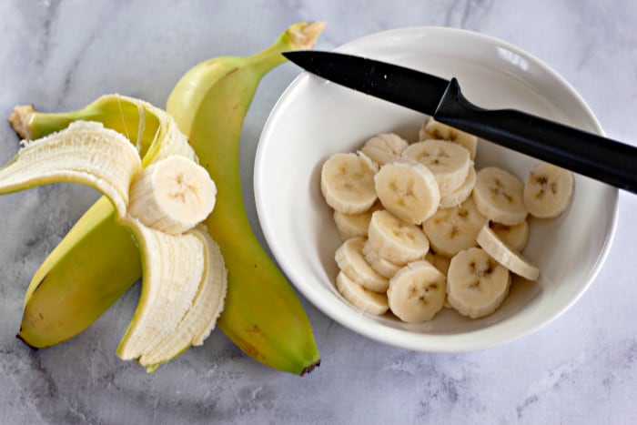 cutting bananas into a white bowl with a black knife
