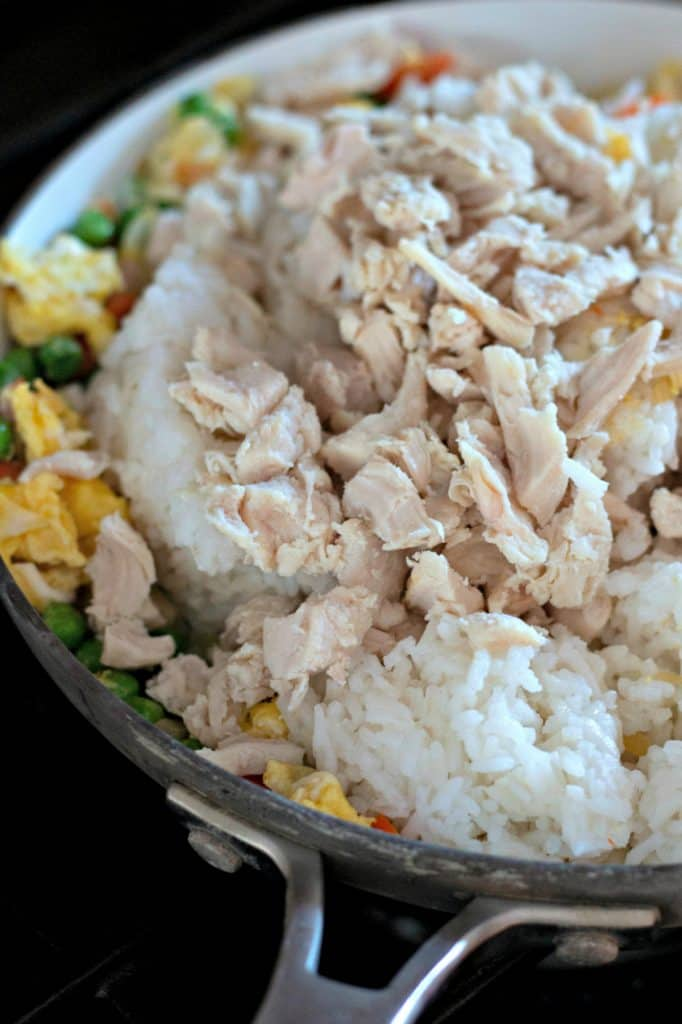 Mixing chicken and rice with vegetables and eggs