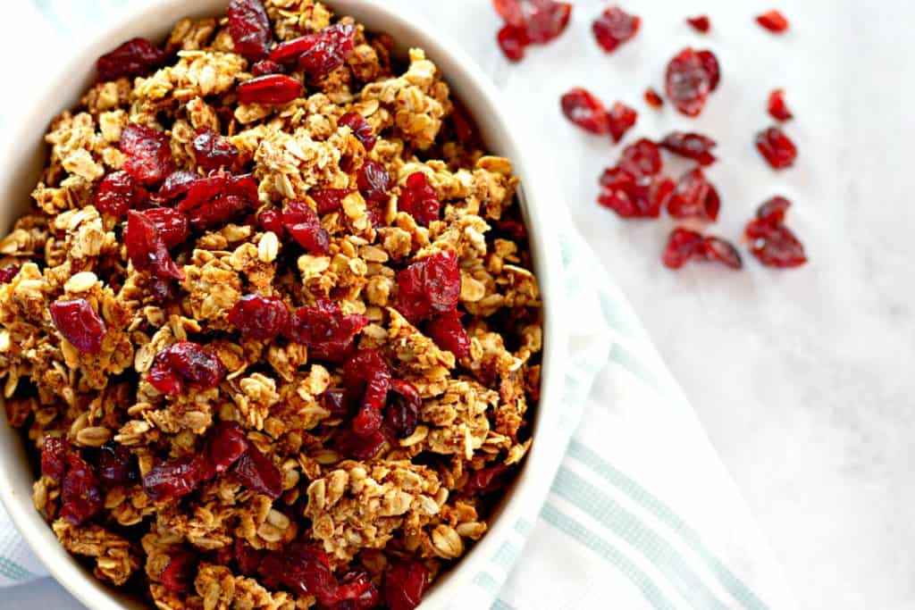 homemade granola in a white bowl with a light blue and white napkin and dried cranberries scattered on the marble counter