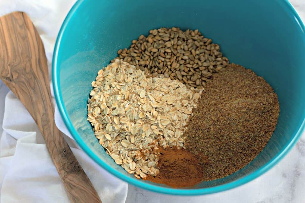 oats, flaxseed, cinnamon, and sunflower seeds in a teal blue bowl with a wooden spoon