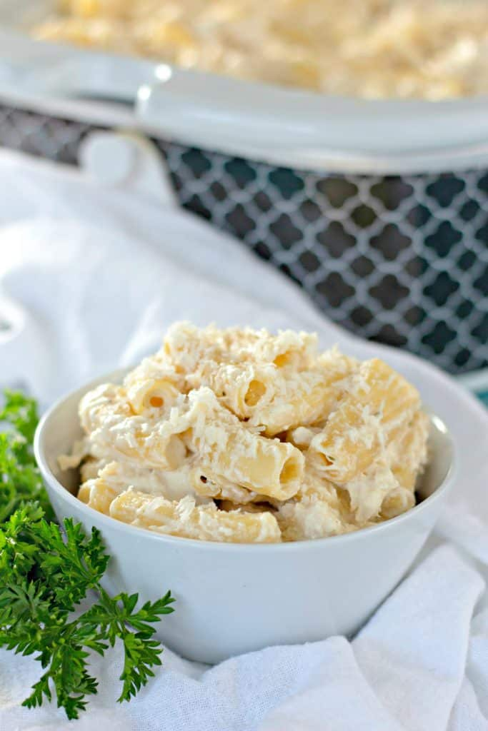 Slow Cooker Chicken Alfredo in a white bowl next to a crockpot