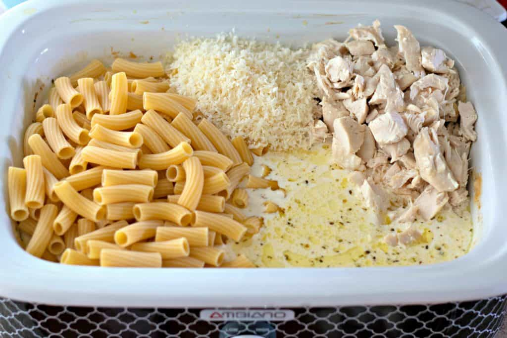 rigatoni, parmesan cheese, and chicken in a slow cooker
