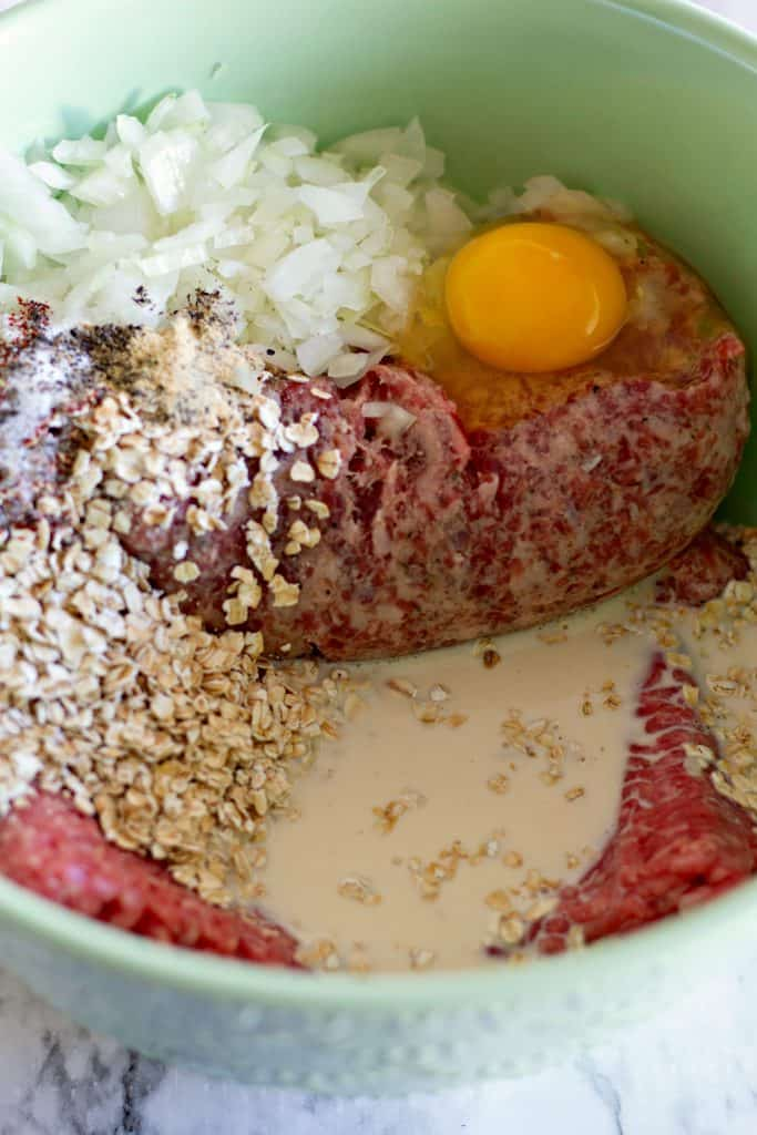 ground beef, ground sausage, egg, oats, onion, evaporated milk, and seasonings in a mint green bowl