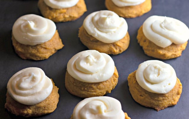 Pumpkin Cookies with Cream Cheese Frosting on a black paper