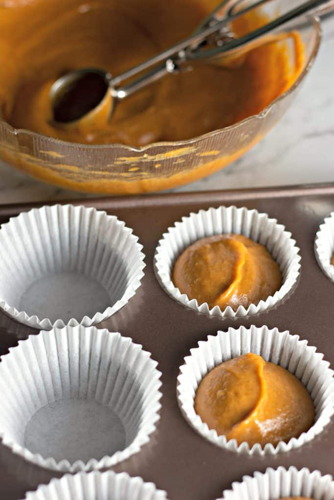 scooping pumpkin cake batter into muffin cups