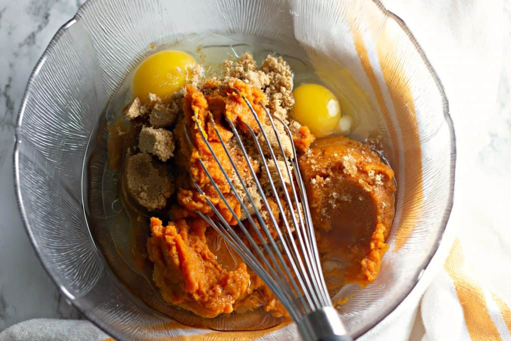 whisking together pumpkin, eggs, oil, and brown sugar in a clear bowl