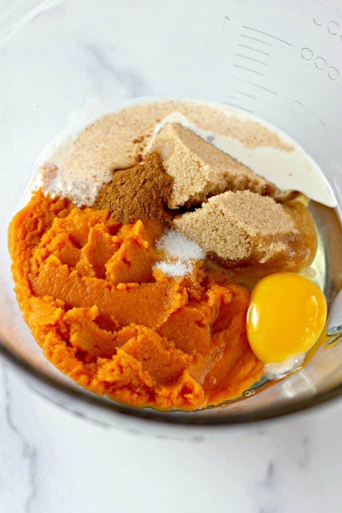 mixing together pumpkin, egg, brown sugar, cream, and pumpkin pie spice in a glass bowl