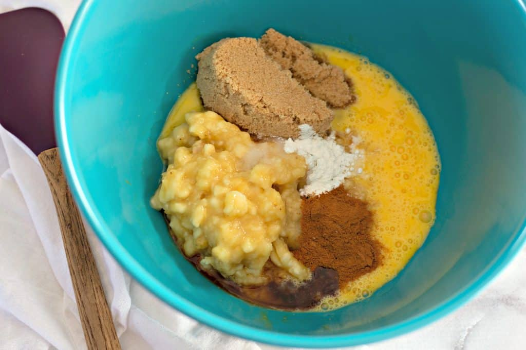 mixing together mashed bananas, eggs, brown sugar, and cinnamon in a teal bowl