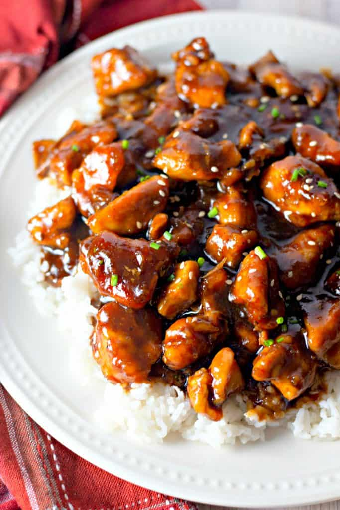 Sweet Bourbon Chicken on a white plate with red napkin