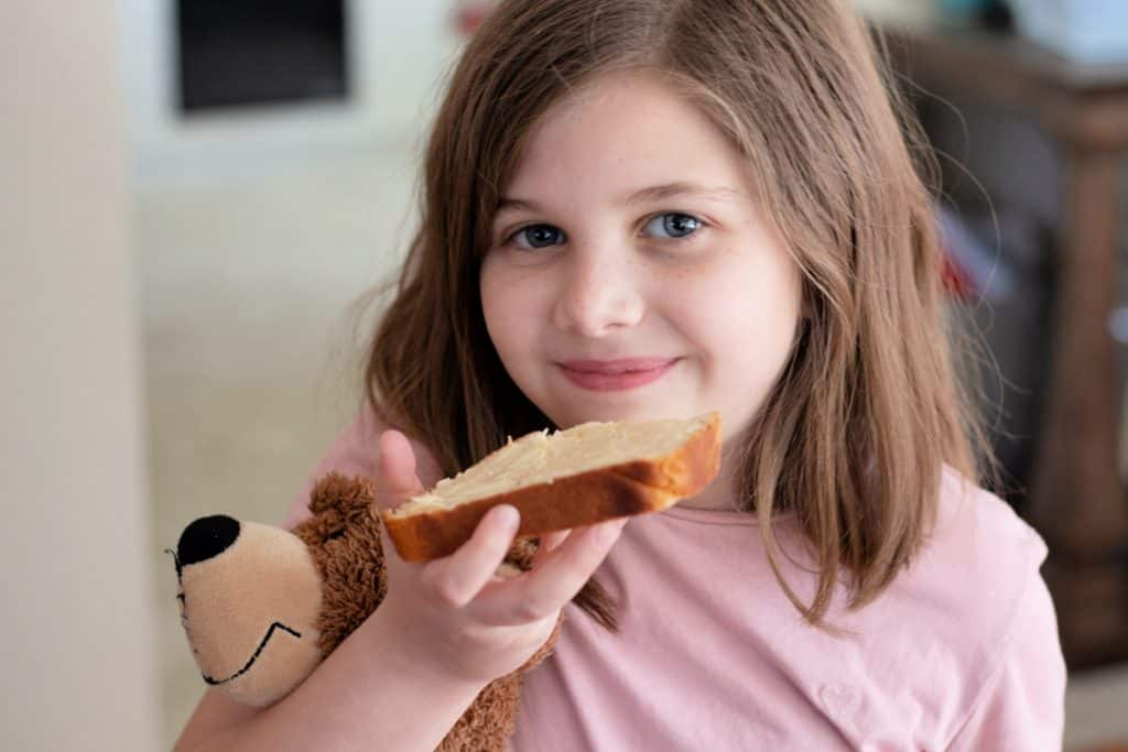child holding a stuffed bear and eating a slice of fresh bread.