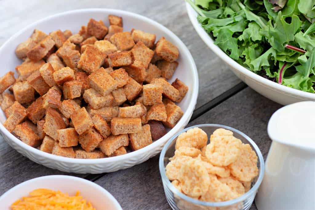 homemade croutons in a white bowl on a table.
