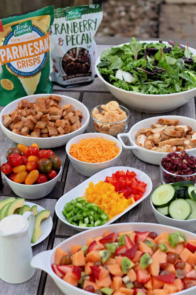 Create Your Own Salad Bar set up on a picnic table.